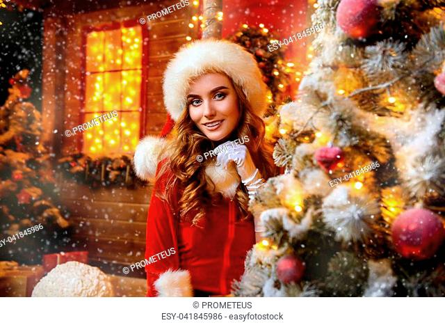 Smiling Santa girl in red body suit and striped stockings poses near the house of Santa, decorated with festive lights. Christmas and New Year concept