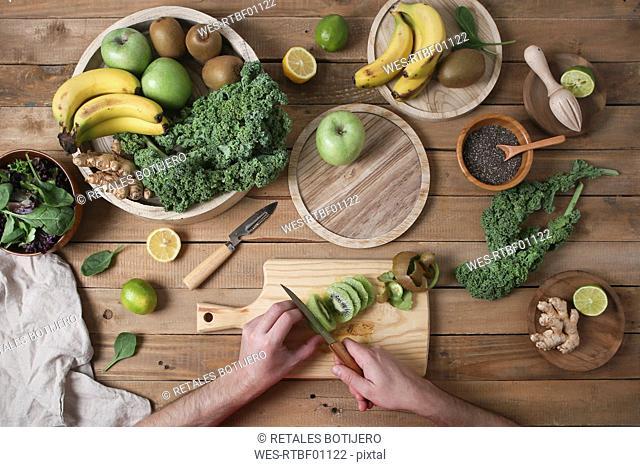 Man preparing green smoothie slicing kiwi