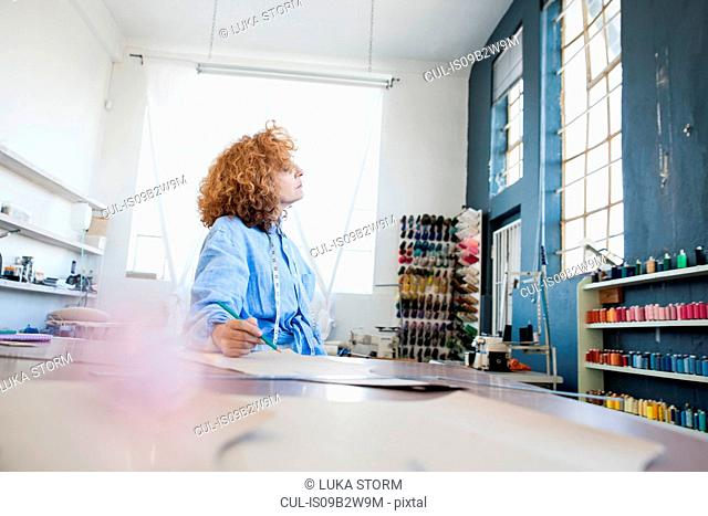 Fashion designer at desk in workshop looking away