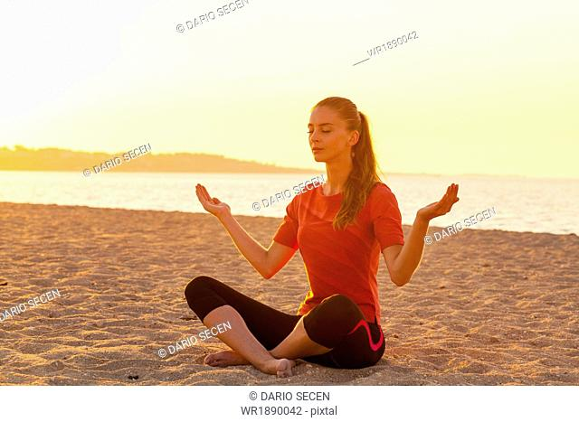 People practising yoga on beach, lotus pose, hands raised
