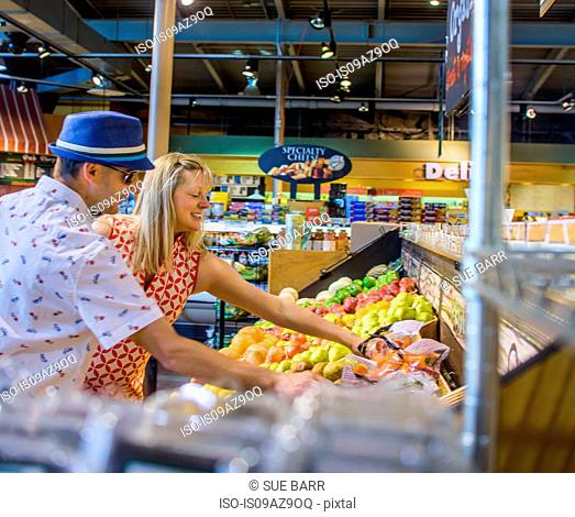 Couple shopping for fruit and vegetables in supermarket