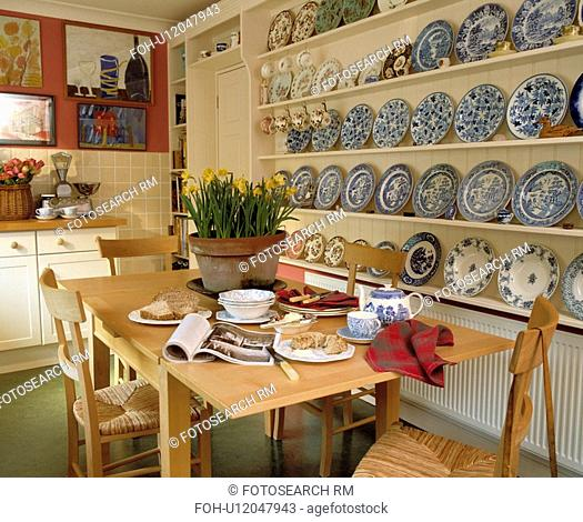 Blue+white plates on white shelves in dining room with table set for breakfast and daffodils in pot