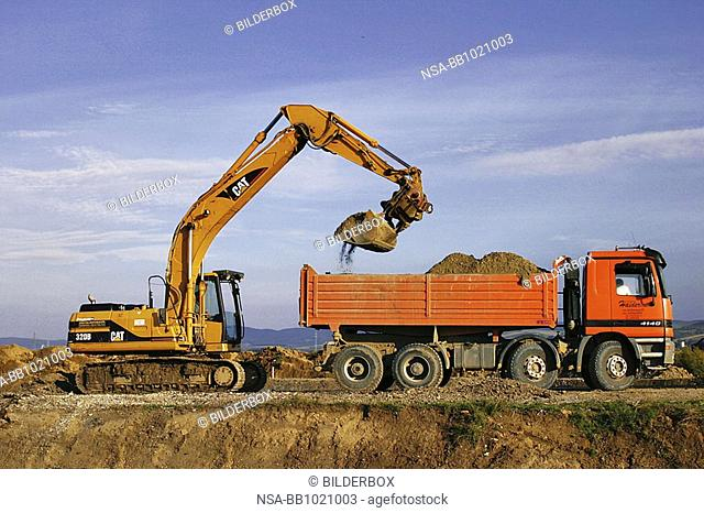Excavator and truck at earthwork