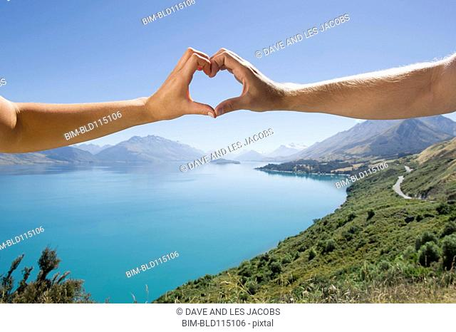 Caucasian couple making heart with hands in rural landscape