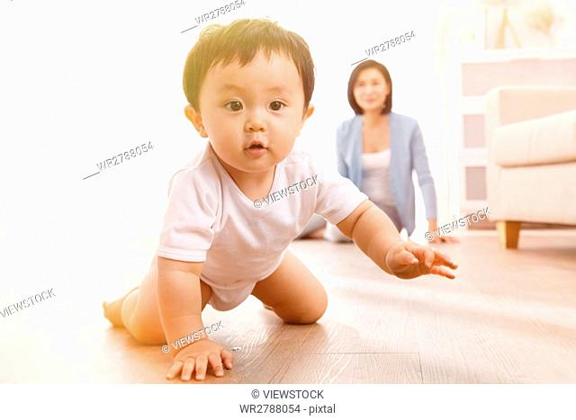 Mother and son crawling on floor