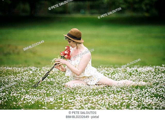 Caucasian woman sitting in field of flowers smelling roses