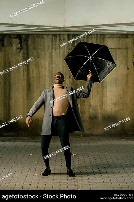 Young man with umbrella looking up while standing on footpath