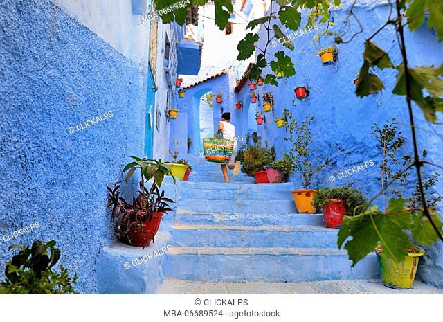 Girl run up the stairs in the medina of Chefchaouen. Tangeri-Tétuan, Morocco, North Africa