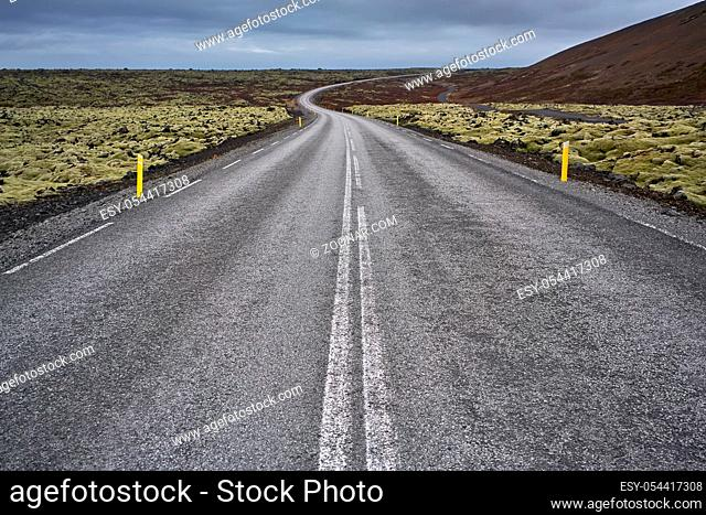 Textured route with orange roadside pillars between the green fields and mountains on the background of the cloudy sky in Iceland. Horizontal