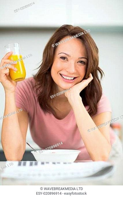 Woman with a bowl of cereals, orange juice and newspaper in kitchen