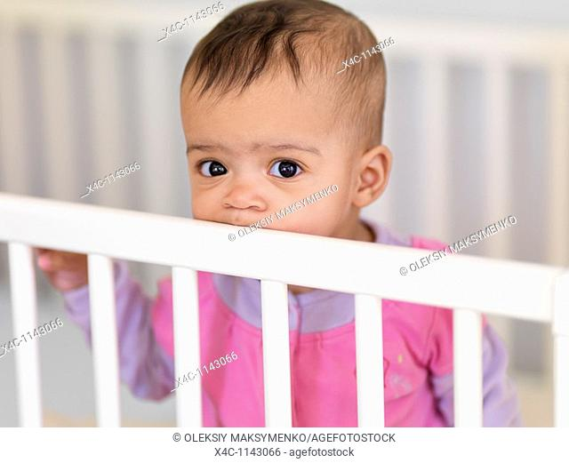 Cute seven month old baby girl in a crib