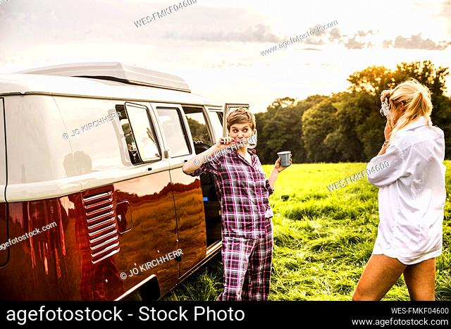 Woman taking picture of friend brushing teeth at a van in rural landscape