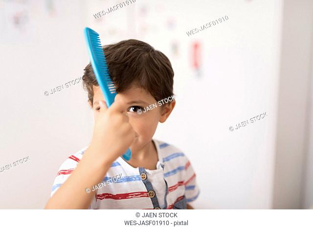 Portrait of little boy combing his hair
