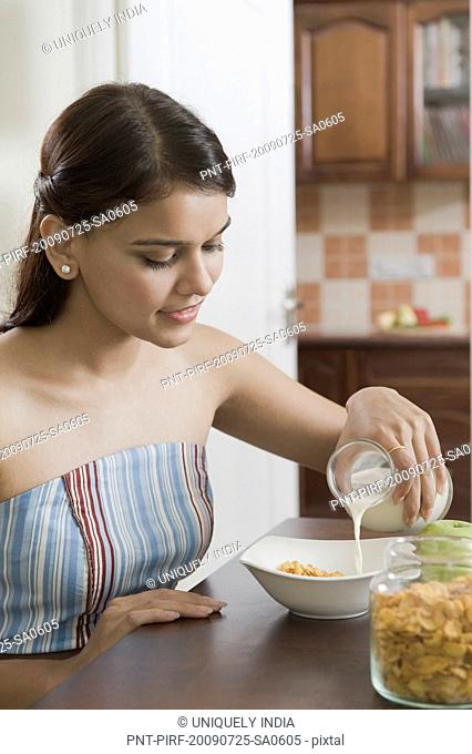 Woman pouring milk on corn flakes into a bowl