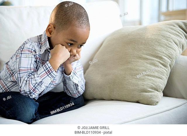 Sulking African American boy sitting on sofa
