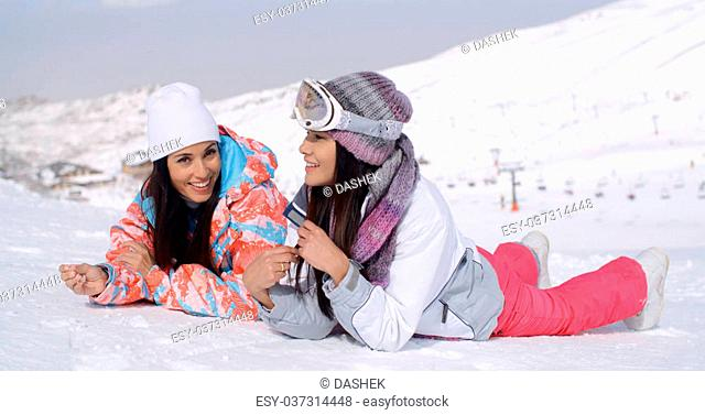 Cute pair of female twins in long black hair and ski clothing giggling while laying down on ground at bottom of ski slope with mountain behind them