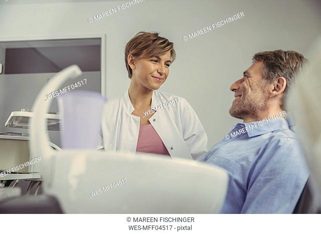 Female dentist talking to her patient before treatment