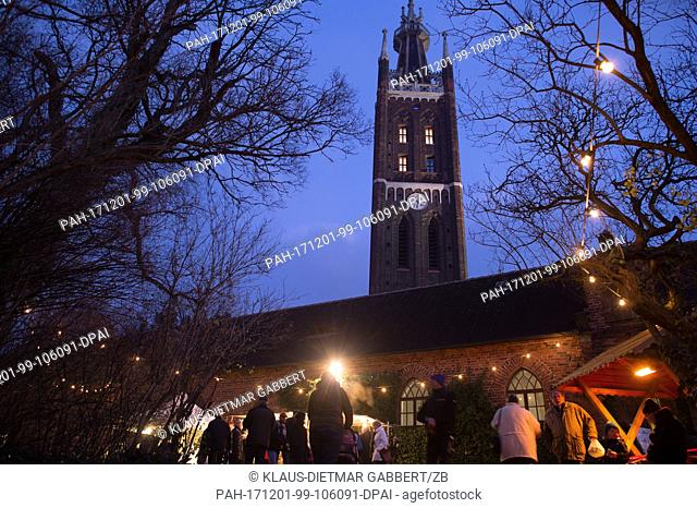 Visitors walk across the Advent market in Oranienbaum-Woerlitz,Germany, 01 December 2017. The tower of the St. Petri Church can be seen in the background