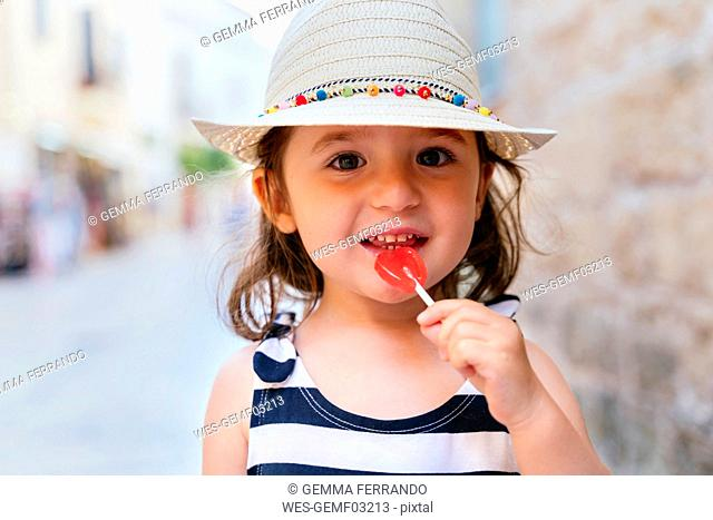 Portrait of smiling little girl with heart-shaped lollipop in summer
