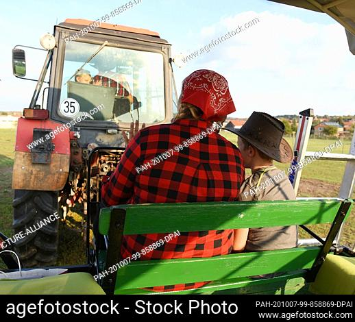 01 October 2020, Saxony, Wermsdorf: Cora Lechner drives to the bison enclosure with her life partner Johannes Boos and her children by tractor