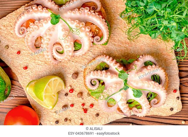 top view of sandwiches with octopus and bread toast decorated lime, avocado, tomato, sprigs of pea leaves and dry peppers
