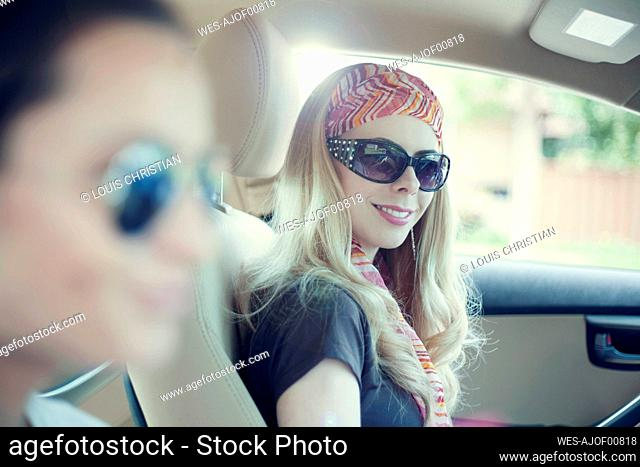 Smiling woman with her female friend in car during road trip