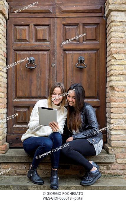 Italy, San Gimignano, two young women sitting in front of entrance door using digital tablet