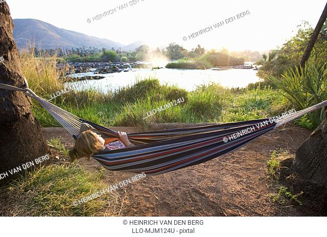 Young woman sleeping in a hammock next to Epupa Falls, Kunene River, Kaokoland, Namibia