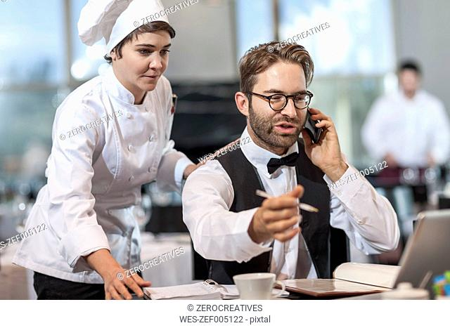 Restaurant chef and manager discussing reservations