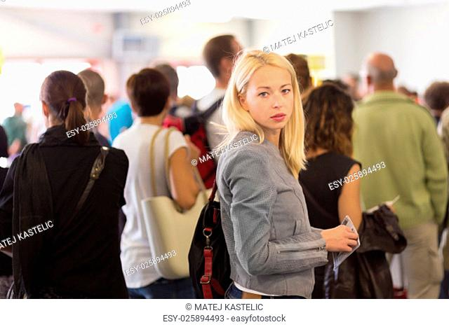 Young blond caucsian woman waiting in line with plain ticket in her hands. Lady standing in a long queue to board a plane