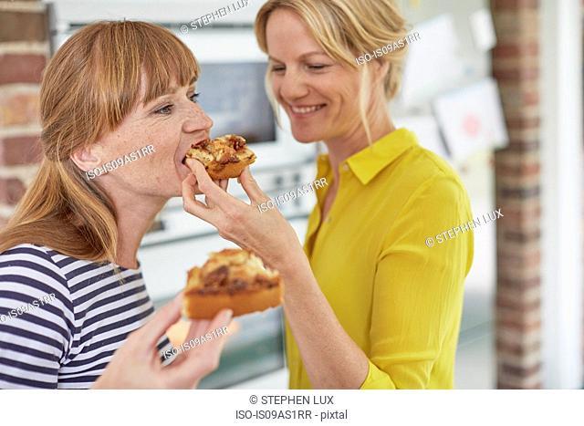 Women eating cake in kitchen