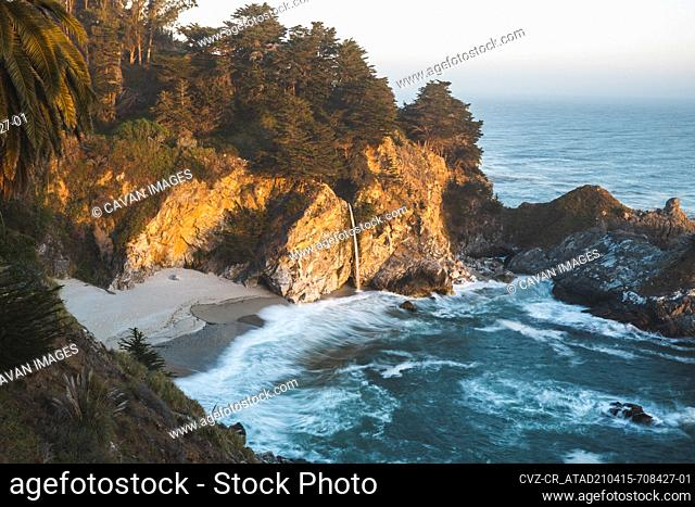 Hazy sunset view of McWay Falls in Big Sur, California