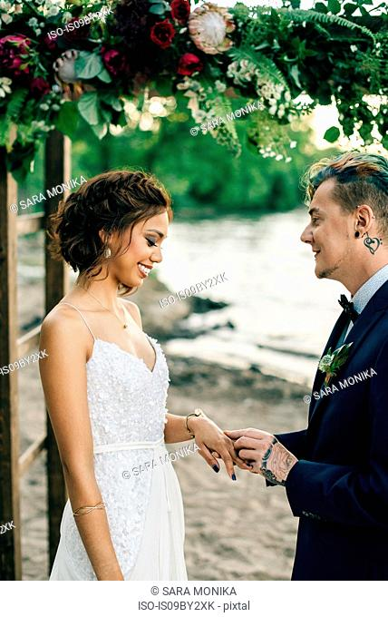 Groom putting on bride's ring on lakeside