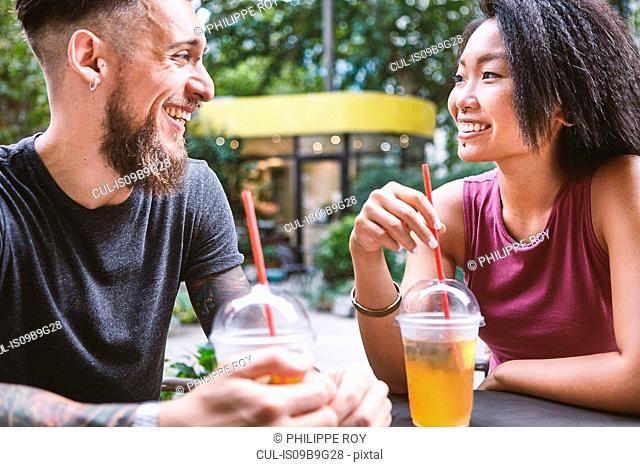 Multi ethnic hipster couple talking at sidewalk cafe, Shanghai French Concession, Shanghai, China
