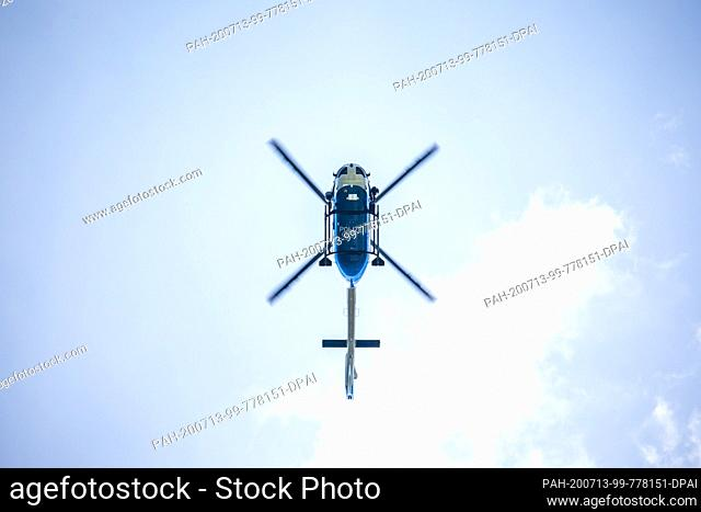 13 July 2020, Baden-Wuerttemberg, Oppenau: A police helicopter flies over the region near Oppenau. With a large contingent