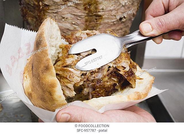 Making a döner kebab: filling pita bread with meat