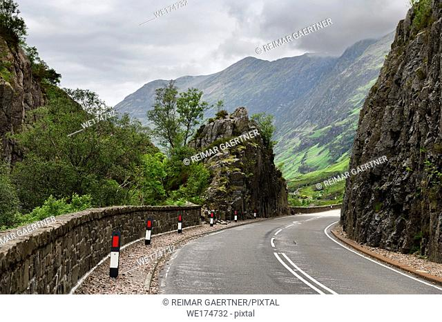 Curving Highway A82 through rock cliffs with Aonach Eagach Ridge mountains north of Glen Coe valley Scottish Highlands Scotland UK