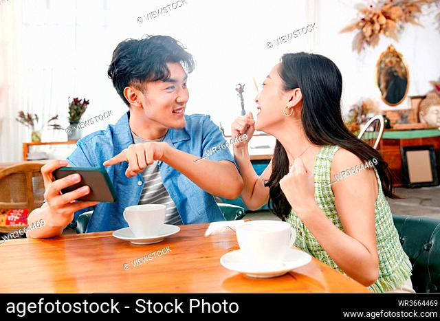 Young couples playing mobile phone at home