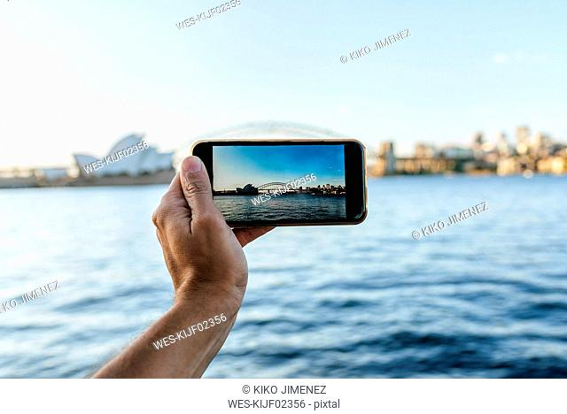 Australia, New South Wales, Sydney, close-up hand of man taking a picture with mobile phone to Sydney