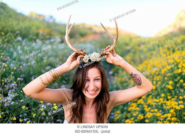 Woman putting on horns in field of wildflowers