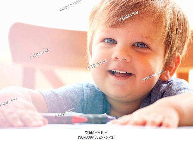 Cropped view of boy with hands on table, looking at camera smiling