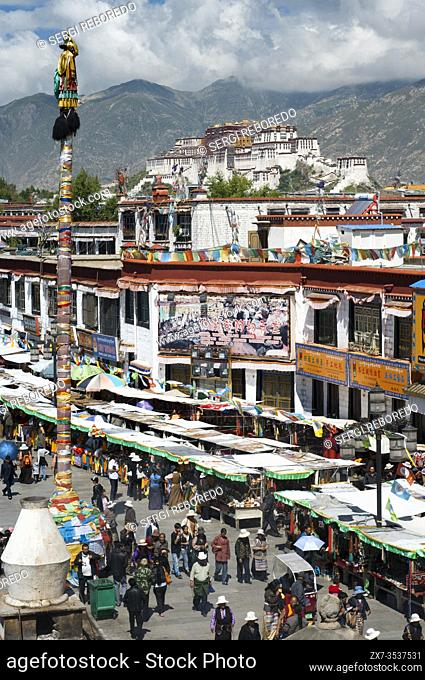 Views from the Jokhang Temple to Barkhor Square and the Potala Palace in the background. In this square, religious objects and tourist trifles are proclaimed at...