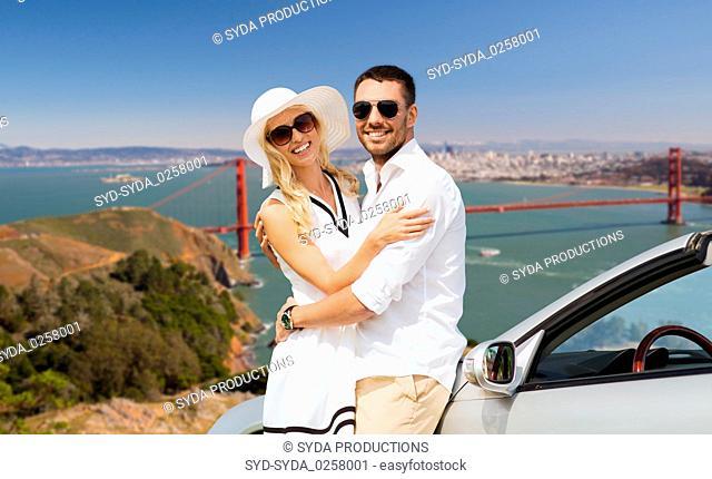 happy couple hugging near convertible car