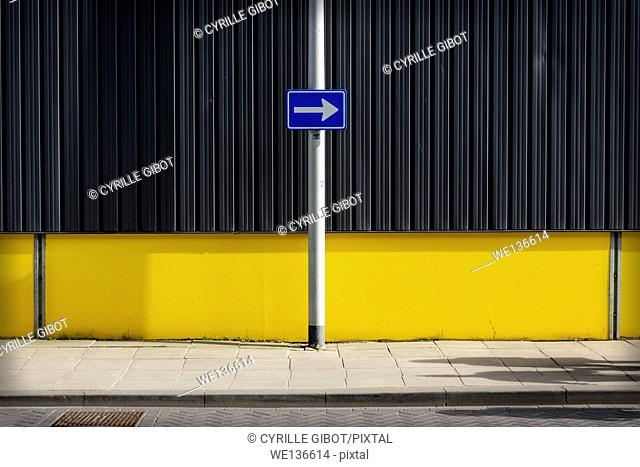 Traffic sign, arrow pointing right against yellow wall