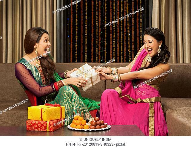 Female friends holding a gift on Diwali