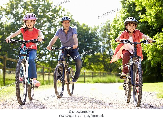Hispanic Father And Children On Cycle Ride In Countryside