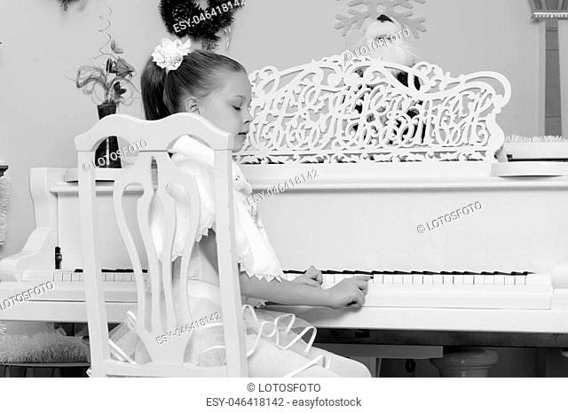 Beautiful, elegant little girl holding hands on the keys of a white Grand piano. Girl playing at the Christmas concert in the music school