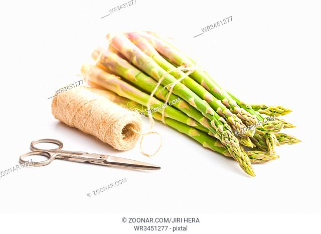 Fresh green asparagus with scissors and thread isolated on white background