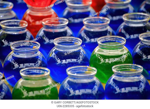 Colourful glass jars filled with coloured liquid lined up in rows