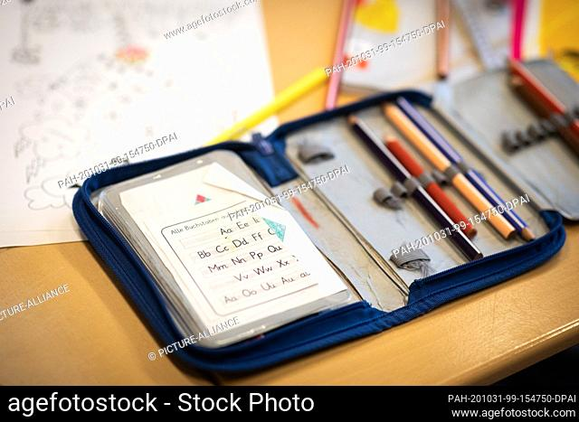 26 October 2020, Hamburg: A piece of paper with the letters of the alphabet is in a pencil case on a table in a 2nd grade class at Hasselbrook primary school